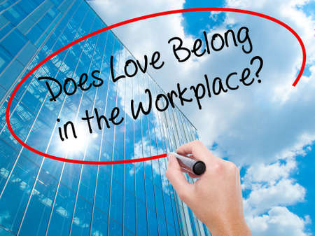 Man Hand writing Does Love Belong in the Workplace? with black marker on visual screen. Business, technology, internet concept. Modern business skyscrapers background. Stock Photo