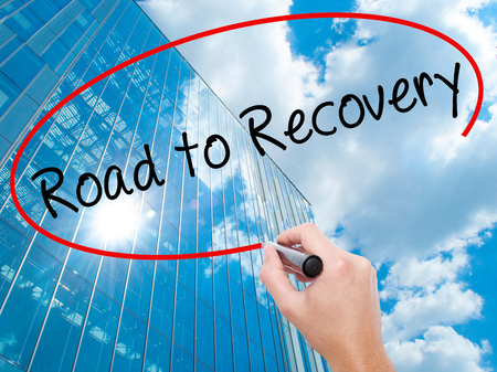 road to recovery: Man Hand writing Road to Recovery with black marker on visual screen. Business, technology, internet concept. Modern business skyscrapers background. Stock Image Stock Photo