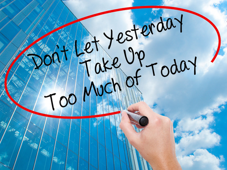 street wise: Man Hand writing Dont Let Yesterday Take Up Too Much of Today with black marker on visual screen.  Business, technology, internet concept. Modern business skyscrapers background. Stock Photo