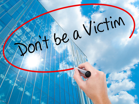 Man Hand writing Dont be a Victim  with black marker on visual screen. Business, technology, internet concept. Modern business skyscrapers background. Stock Photo