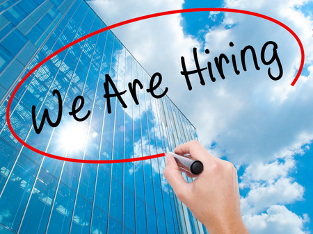 recruit help: Man Hand writing We Are Hiring  with black marker on visual screen. Business, technology, internet concept. Modern business skyscrapers background. Stock Image