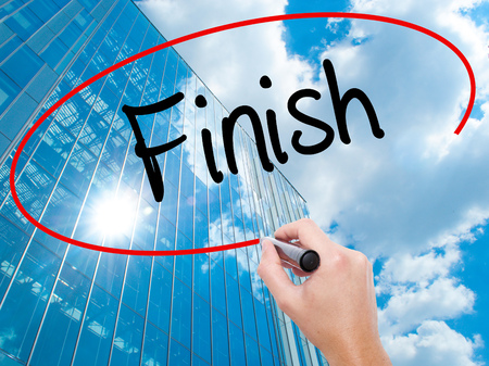 complete crossing: Man Hand writing  Finish with black marker on visual screen.  Business, technology, internet concept. Modern business skyscrapers background. Stock Photo