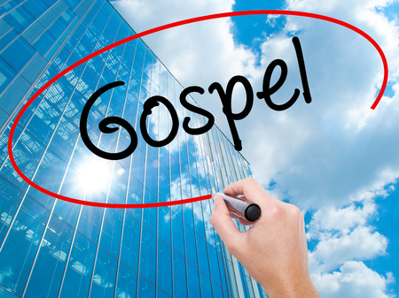 Man Hand writing Gospel  with black marker on visual screen.  Business, technology, internet concept. Modern business skyscrapers background. Stock Photo