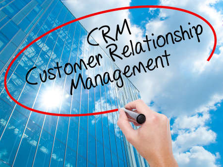 Man Hand writing CRM Customer Relationship Management  with black marker on visual screen. Business, technology, internet concept. Modern business skyscrapers background. Stock Photo