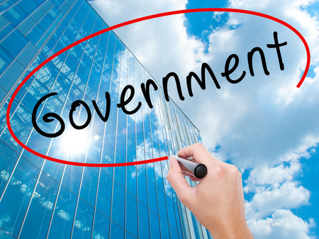 legislator: Man Hand writing Government with black marker on visual screen. Business, technology, internet concept. Modern business skyscrapers background. Stock Image