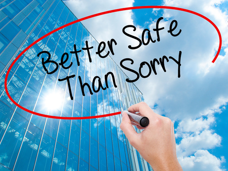 Man Hand writing Better Safe Than Sorry with black marker on visual screen.  Business, technology, internet concept. Modern business skyscrapers background. Stock Photo Stock Photo