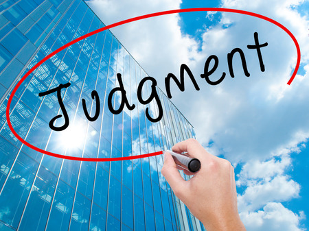 Man Hand writing Judgment with black marker on visual screen. Business, technology, internet concept. Modern business skyscrapers background. Stock Image