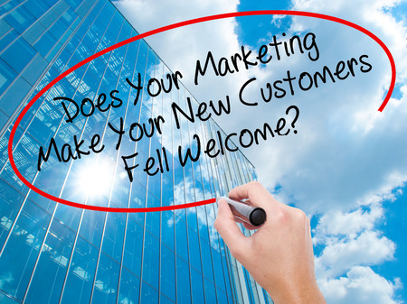 Man Hand writing Does Your Marketing Make Your New Customers Fell Welcome?  with black marker on visual screen. Business, technology, internet concept. Modern business skyscrapers background. Stock Photo