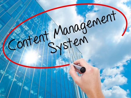Man Hand writing Content Management System  with black marker on visual screen. Business, technology, internet concept. Modern business skyscrapers background. Stock Photo Stock Photo