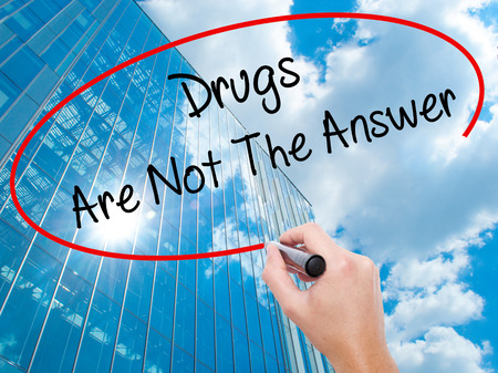 Man Hand writing Drugs Are Not The Answer with black marker on visual screen. Business, technology, internet concept. Modern business skyscrapers background. Stock Photo Stock Photo