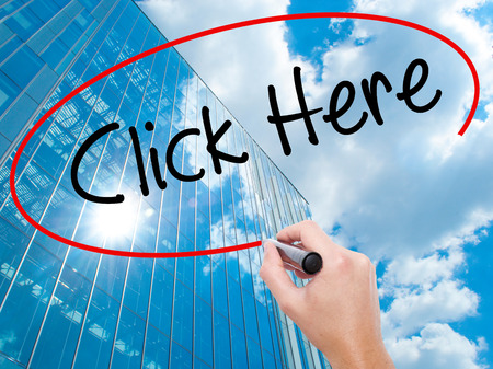 Man Hand writing Click Here with black marker on visual screen. Business, technology, internet concept. Modern business skyscrapers background. Stock Photo Stock Photo