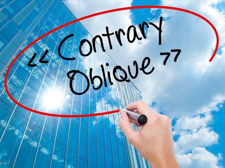 contrary: Man Hand writing Contrary - Oblique with black marker on visual screen.  Business, technology, internet concept. Modern business skyscrapers background. Stock Photo