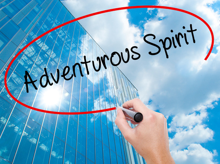 Man Hand writing Adventurous Spirit with black marker on visual screen. Business, technology, internet concept. Modern business skyscrapers background. Stock Photo