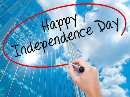 Man Hand writing happy Independence Day with black marker on visual screen. Business, technology, internet concept. Modern business skyscrapers background. Stock Image
