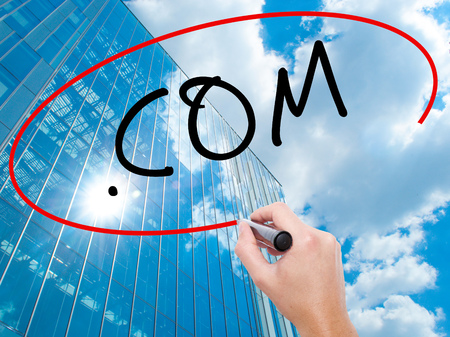suffix: Man Hand writing .COM with black marker on visual screen. Business, technology, internet concept. Modern business skyscrapers background. Stock Image