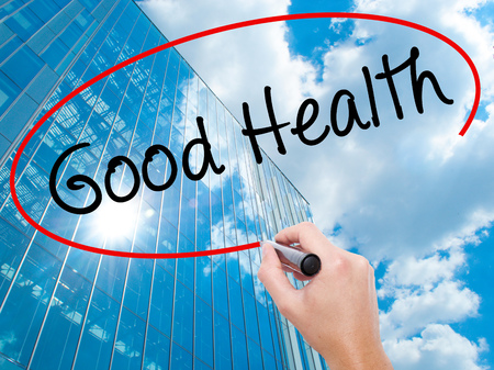 Man Hand writing Good Health with black marker on visual screen. Business, technology, internet concept. Modern business skyscrapers background. Stock Image