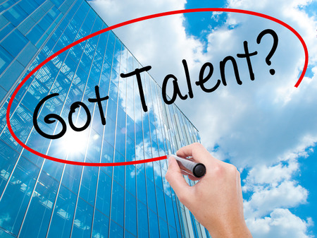abilities: Man Hand writing Got Talent? with black marker on visual screen. Business, technology, internet concept. Modern business skyscrapers background. Stock Image Stock Photo