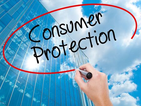 Man Hand writing Consumer Protection  with black marker on visual screen.  Business, technology, internet concept. Modern business skyscrapers background. Stock Photo