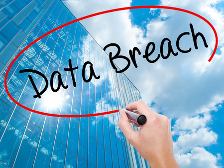 Man Hand writing Data Breach with black marker on visual screen. Business, technology, internet concept. Modern business skyscrapers background. Stock Photo