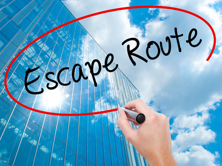 breakout: Man Hand writing Escape Route with black marker on visual screen. Business, technology, internet concept. Modern business skyscrapers background. Stock Photo