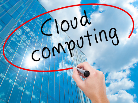 Man Hand writing Cloud computing with black marker on visual screen. Business, technology, internet concept. Modern business skyscrapers background. Stock Image