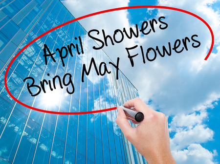 Man Hand writing April Showers Bring May Flowers with black marker on visual screen. Business, technology, internet concept. Modern business skyscrapers background. Stock Photo