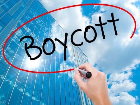 denying: Man Hand writing Boycott with black marker on visual screen.  Business, technology, internet concept. Modern business skyscrapers background. Stock Photo