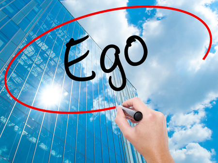 Man Hand writing Ego with black marker on visual screen.  Business, technology, internet concept. Modern business skyscrapers background. Stock Photo