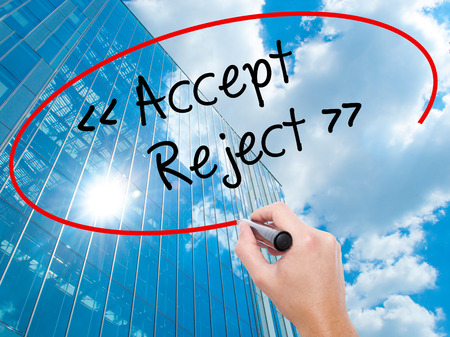 Man Hand writing Accept - Reject  with black marker on visual screen.  Business, technology, internet concept. Modern business skyscrapers background. Stock Photo Stock Photo