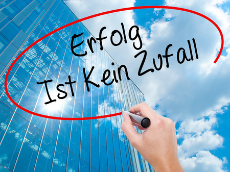 Man Hand writing Erfolg Ist Kein Zaufall (Success Is No Accident in German) with black marker on visual screen.  Business, technology, internet concept. Modern business skyscrapers background. Stock Photo Stock Photo