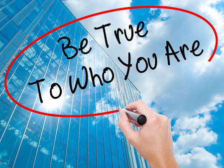 Man Hand writing Be True To Who You Are with black marker on visual screen. Business, technology, internet concept. Modern business skyscrapers background. Stock Photo