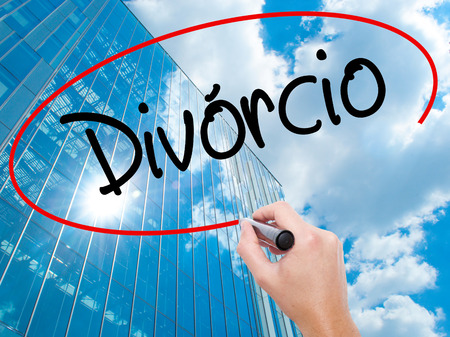 Man Hand writing Divorcio (Divorce in Portuguese) with black marker on visual screen.  Business, technology, internet concept. Modern business skyscrapers background. Stock Photo