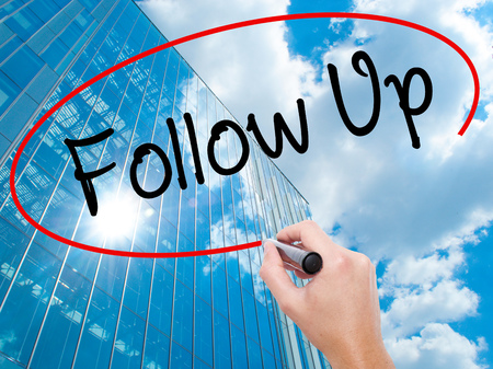 Man Hand writing Follow Up with black marker on visual screen. Business, technology, internet concept. Modern business skyscrapers background. Stock Photo Stock Photo