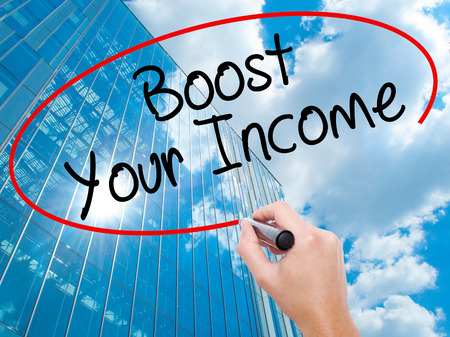 emolument: Man Hand writing Boost Your Income with black marker on visual screen. Business, technology, internet concept. Modern business skyscrapers background. Stock Photo Stock Photo