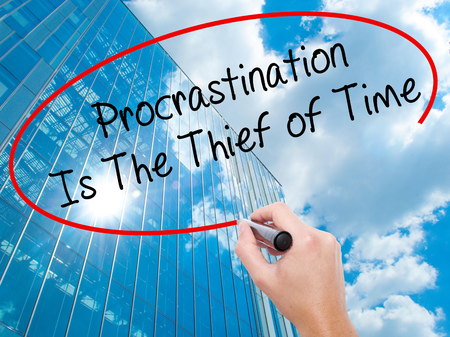 Man Hand writing  Procrastination Is The Thief of Time with black marker on visual screen. Business, technology, internet concept. Modern business skyscrapers background. Stock Image
