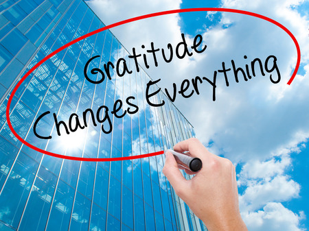 Man Hand writing Gratitude Changes Everything with black marker on visual screen. Business, technology, internet concept. Modern business skyscrapers background. Stock Photo