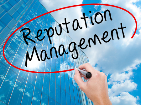Man Hand writing Reputation Management with black marker on visual screen. Business, technology, internet concept. Modern business skyscrapers background. Stock Image