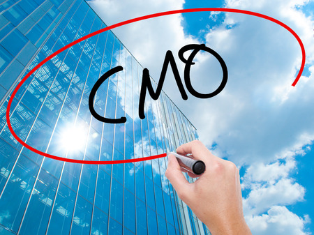 chief executive officer: Man Hand writing CMO (Chief Marketing Officer)   with black marker on visual screen.  Business, technology, internet concept. Modern business skyscrapers background. Stock Photo