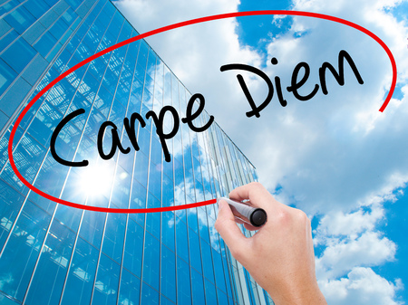 Man Hand writing Carpe Diem with black marker on visual screen. Business, technology, internet concept. Modern business skyscrapers background. Stock Photo