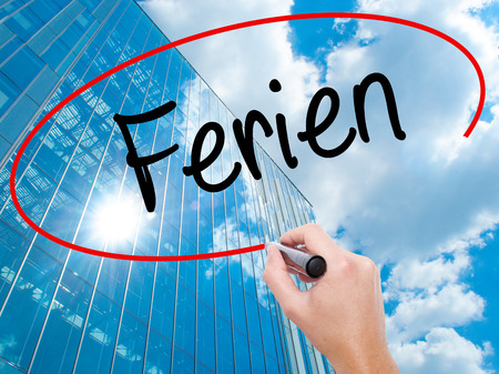 rescheduling: Man Hand writing Ferien  (Vacation in German) with black marker on visual screen.  Business, technology, internet concept. Modern business skyscrapers background. Stock Photo