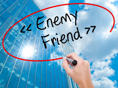 Man Hand writing Enemy - Friend with black marker on visual screen.  Business, technology, internet concept. Modern business skyscrapers background. Stock Photo