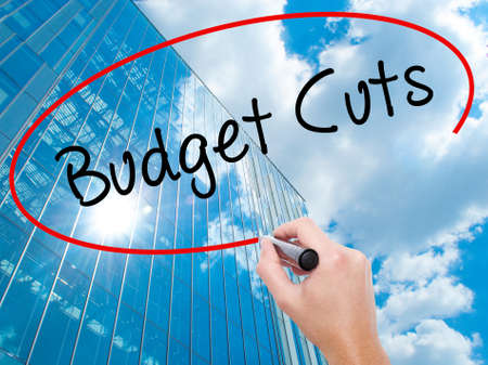 Man Hand writing Budget Cuts with black marker on visual screen.  Business, technology, internet concept. Modern business skyscrapers background. Stock Photo