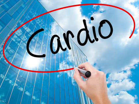 Man Hand writing Cardio with black marker on visual screen.  Business, technology, internet concept. Modern business skyscrapers background. Stock Photo