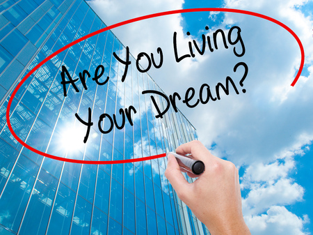 jargon: Man Hand writing Are You Living Your Dream? with black marker on visual screen. Business, technology, internet concept. Modern business skyscrapers background. Stock Photo Stock Photo