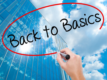 Man Hand writing Back to Basics with black marker on visual screen. Business, technology, internet concept. Modern business skyscrapers background. Stock Photo Stock Photo
