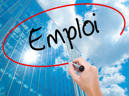 seeking solution: Man Hand writing Emploi (Employment in French) with black marker on visual screen.  Business, technology, internet concept. Modern business skyscrapers background. Stock Photo