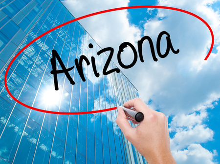 Man Hand writing  Arizona  with black marker on visual screen.  Business, technology, internet concept. Modern business skyscrapers background. Stock Photo Stock Photo