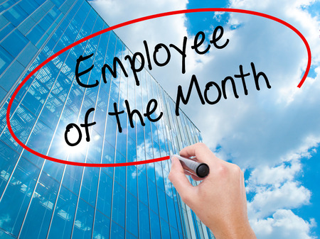 Man Hand writing Employee of the Month  with black marker on visual screen. Business, technology, internet concept. Modern business skyscrapers background. Stock Photo Stock Photo