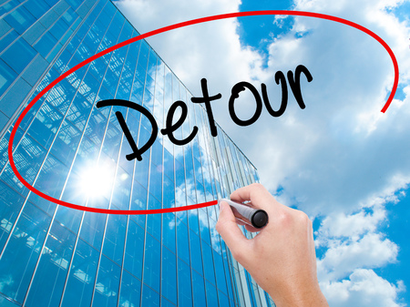 Man Hand writing Detour  with black marker on visual screen. Business,  internet concept. Modern business skyscrapers background. Stock Photo