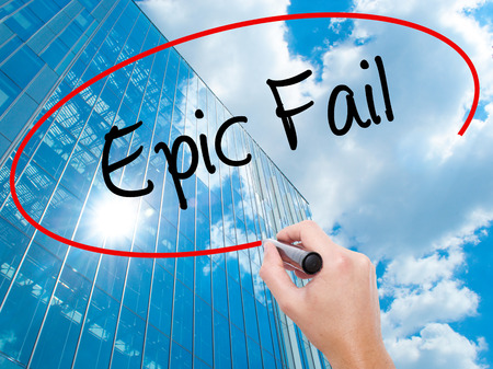 blunder: Man Hand writing Epic Fail with black marker on visual screen.  Business, technology, internet concept. Modern business skyscrapers background. Stock Photo
